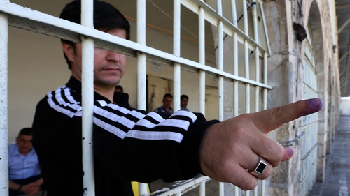 An Iraqi prisoner shows his ink-stained finger after voting in the election at a prison in Arbil