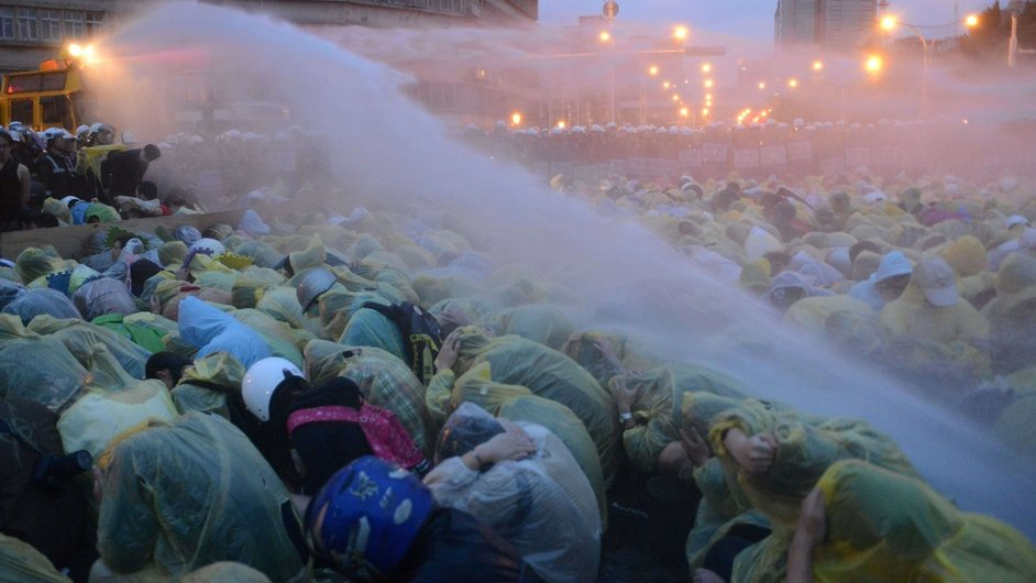 Protesters squat on the ground as water is sprayed at them outside Taipei Railway Station during an anti-nuclear demonstration
