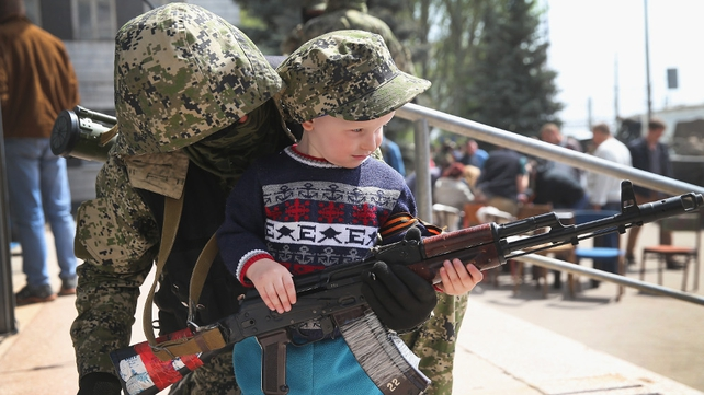A pro-Russian miliant shows a child his rifle in Kostyantynivka