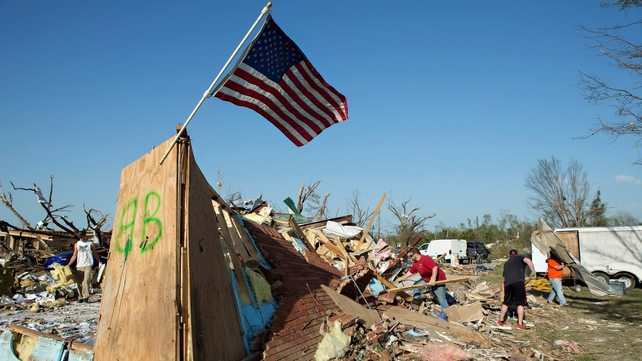 Homeowners and volunteers clean up the damage after a tornado in Alabama