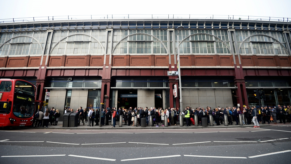 People queue for a bus outside the Waterloo tube station in London, where a 48-hour tube strike has hit hundreds of thousands of commuters