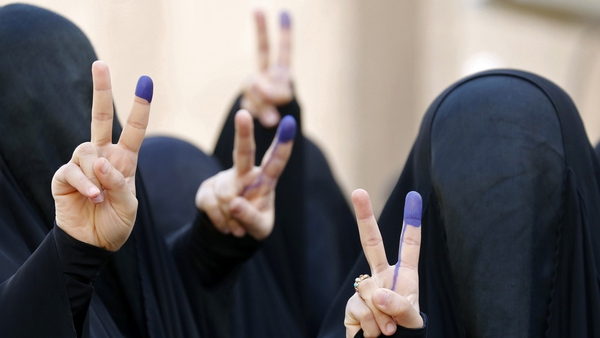 Iraqi women flash the sign for victory with their ink-stained fingers after casting their vote in Baghdad