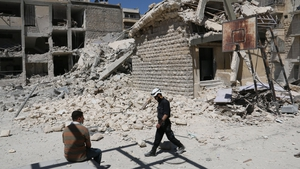 A rusty basketball hoop stands amid destruction in the courtyard  of the school destroyed by the air strikes