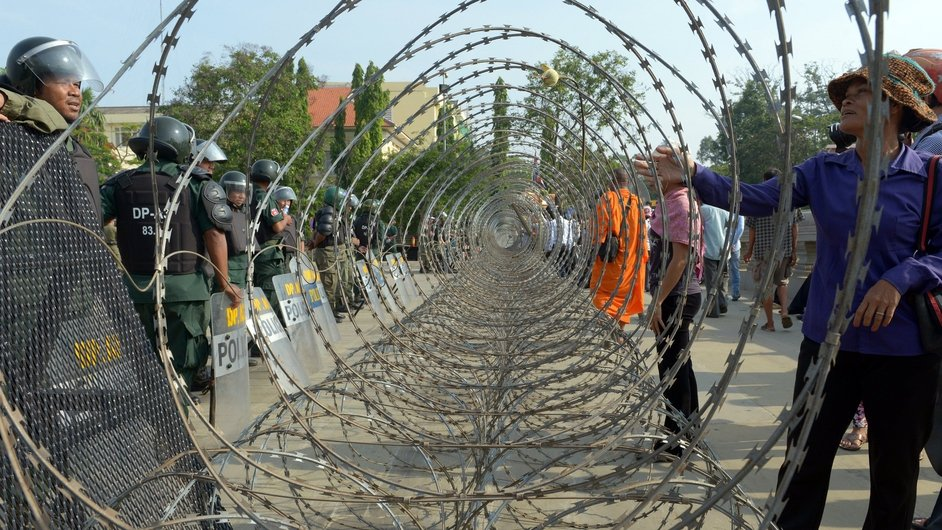 A Cambodian woman stands next to barbed wire as she talks to the police during a rally in Phnom Penh