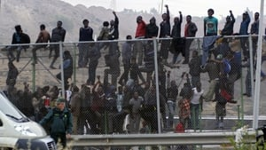 Dozens of immigrants climb on to the fence at the border between Morocco and Melilla (Pic: EPA)