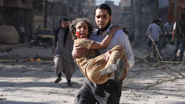 A man carries a wounded girl following an explosion in the northern Syrian city of Aleppo