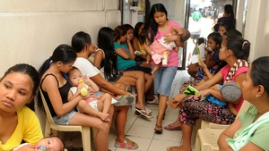 Mothers with children queue at Likhaan Center for Women's Health for free family planning assistance