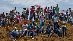 Miners look at the rescue operations after a gold mine collapsed in San Antonio, rural Colombia