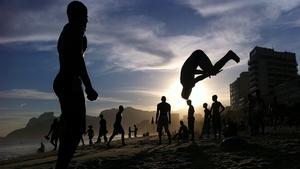 A man performs a flip on Ipanema Beach, Brazil