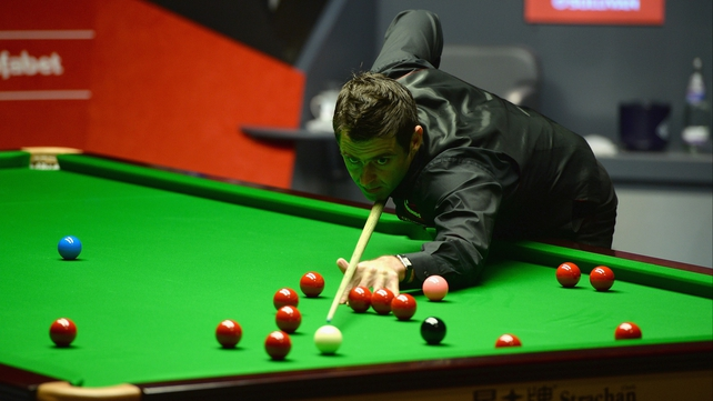 Ronnie O'Sullivan lines up a shot against Barry Hawkins