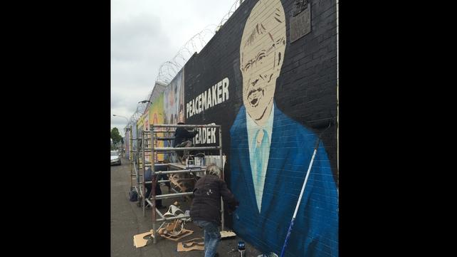 People work on a mural of Mr Adams