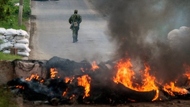 An armed pro-Russian rebel walks behind a burning barricade on a checkpoint in Slaviansk