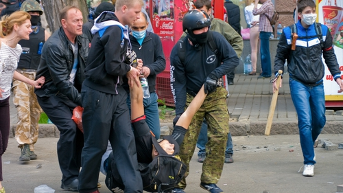 Pro-Russian activists carry a wounded man during their clash with supporters of a 'Single Ukraine', in Odessa
