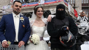 A couple on their wedding day poses with a masked and armed man at the barricades in the centre of Donetsk