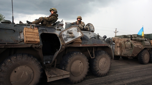 Unmarked soldiers wait on the road as separatists block the Kramatorsk road