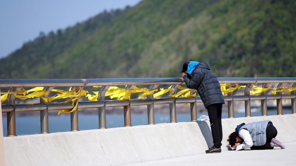 Family members of one of the passengers of the sunken Sewol ferry bow in prayer at Jindo Island, southwestern South Korea