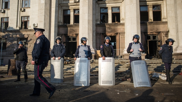 Ukrainian police stand outside the burnt trade union building in Odessa
