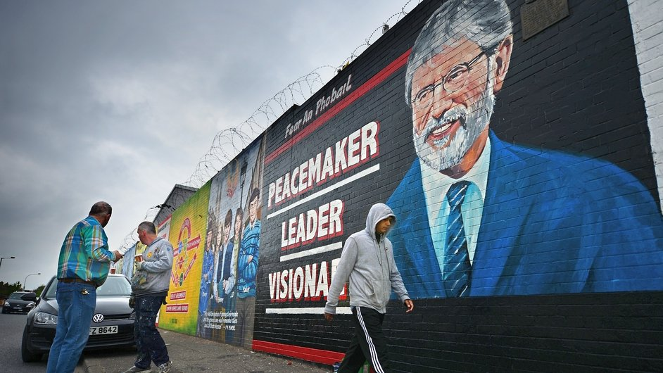 Members of the public pass a new mural of Sinn Féin leader Gerry Adams painted on a wall on the Falls Road in Belfast