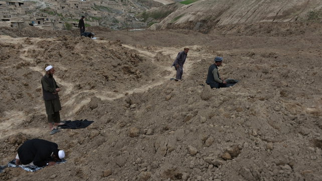 Afghan villagers pray at the scene in Argo district of Badakhshan province