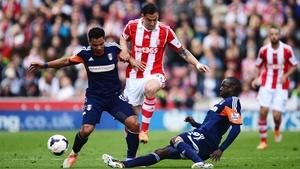 Geoff Cameron of Stoke City rides the challenge of Kieran Richardson (L) and Mahamadou Diarra