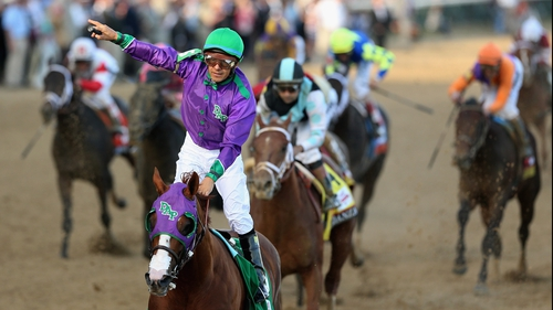 Jockey Victor Espinoza celebrates atop of California Chrome after crossing the finish line to win the Kentucky Derby
