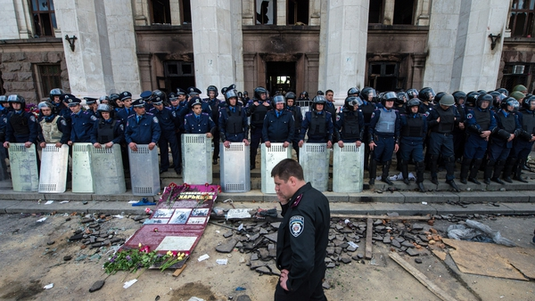 Policemen stand guard outside the charred trade union building in the southern Ukrainian city of Odessa