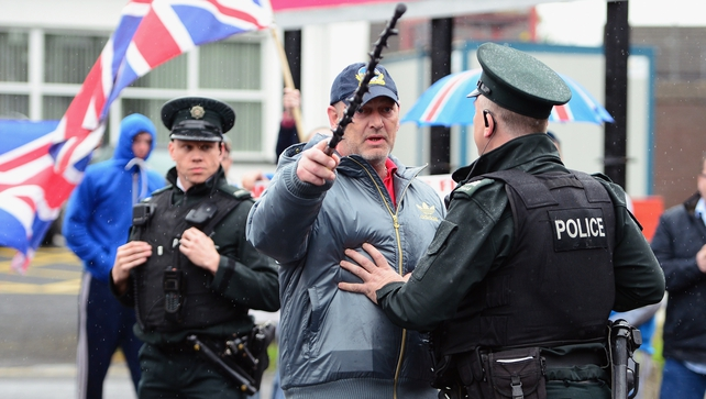 A policeman speaks to a loyalist aoutside the Antrim Police station where Gerry Adams is being questioned