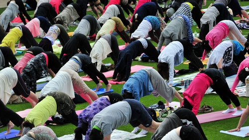Japanese yoga students participate in an outdoor yoga class at a park in Tokyo