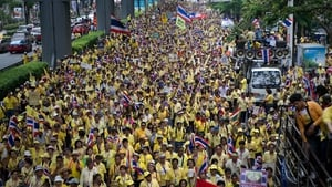 Anti-government protesters march  in Bangkok to mark the 64th anniversary of Thai King Bhumibol Adulyadej's coronation