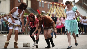 A team rolls a wooden 'cheese' during the Stilton Village Festival cheese rolling competition in Stilton, England