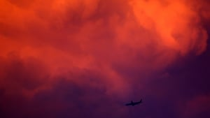 An aircraft flies at the base of a large glowing storm cloud lit by the setting sun in the skies above Bangkok, Thailand