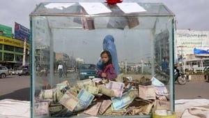 Afghan people pass by a donation box for the victims of last week's landslide in Afghanistan