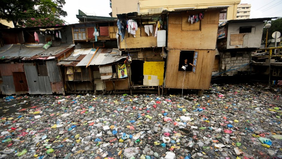 A Filipino informal settler is seen inside a shanty dwelling along a polluted river in Manila, Philippines