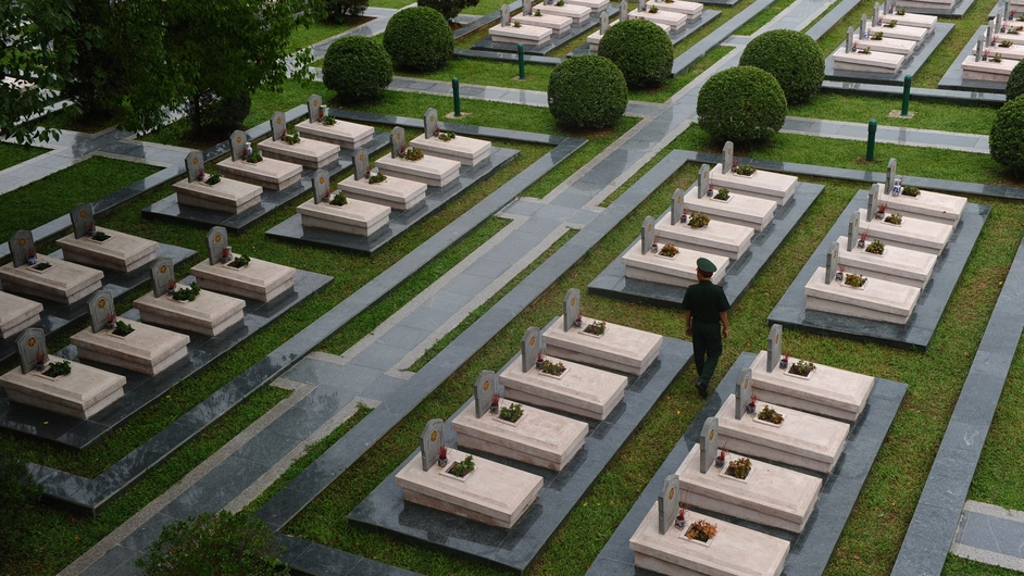 A soldier walks among graves of Vietnamese soldiers killed during the battle of Dien Bien Phu