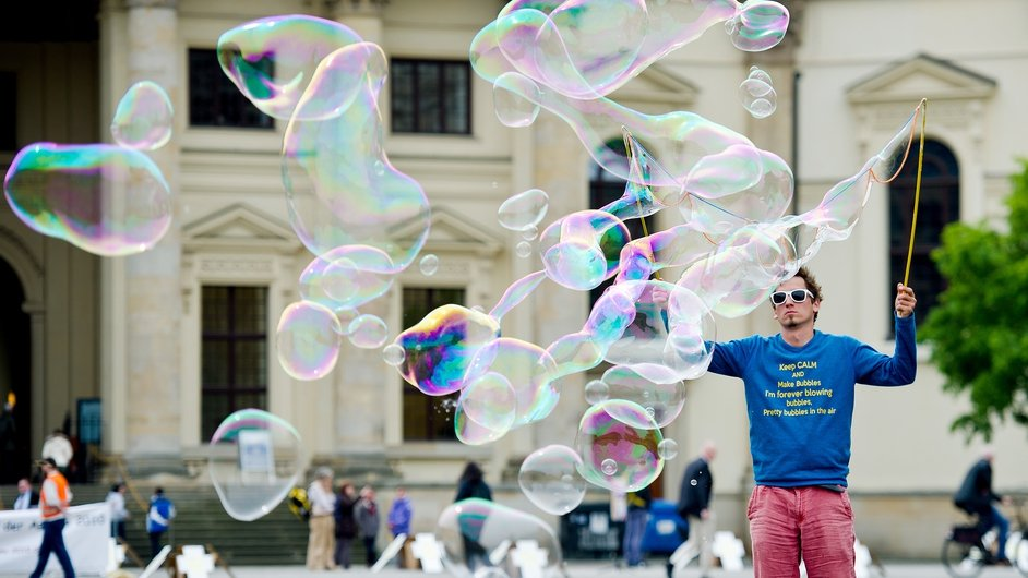 A street artist makes soap bubbles on Gendarmenmarkt square in Berlin, Germany