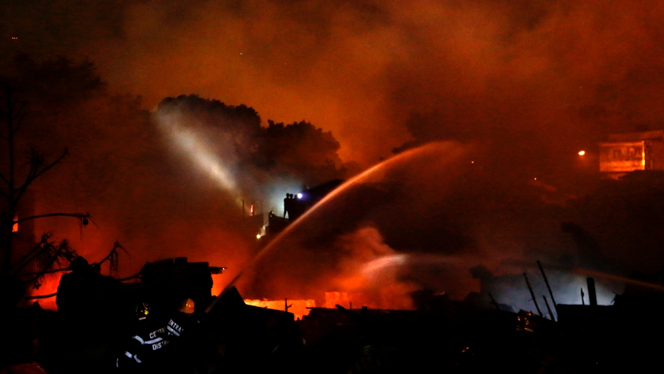 Filipino firemen use water cannon to extinguish a fire in a residential slum area in Quezon City, east of Manila, Philippines