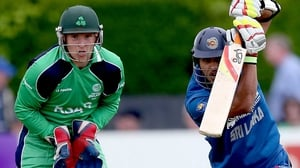 Ireland wicketkeeper Gary Wilson watches as Dinesh Chandimal bats the ball away