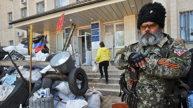 An armed pro-Russian militant guards a barricade outside the regional state building in Kramatorsk, eastern Ukraine