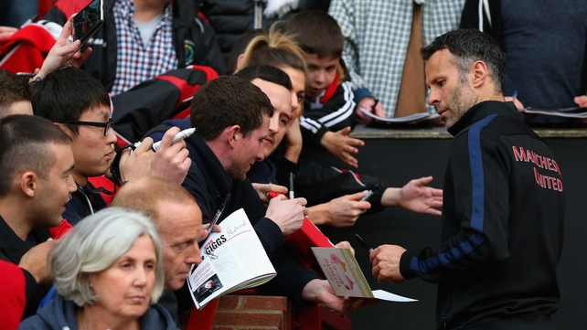 Manchester United caretaker manager Ryan Giggs signs autographs prior to the match