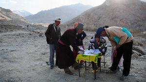 Indian polling officials and residents look at voting registration lists outside a polling station high up in the village of Phyang Fulung, a community overlooking the Indus river valley