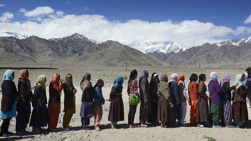 Indian voters line up to vote outside a small rural school in Shushot Yongma, a small enclave on the Indus river valley near the northern city of Leh