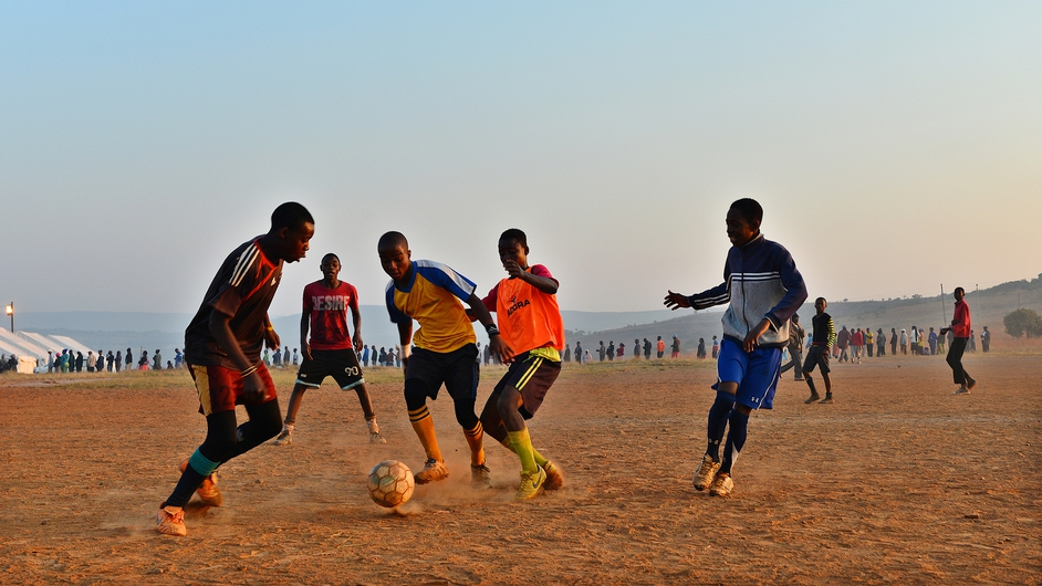 Local boys play football as people queue to vote in Pretoria, South Africa