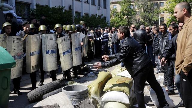 A pro-Russian supporter talks to Ukrainian policemen in Mariupol, Ukraine