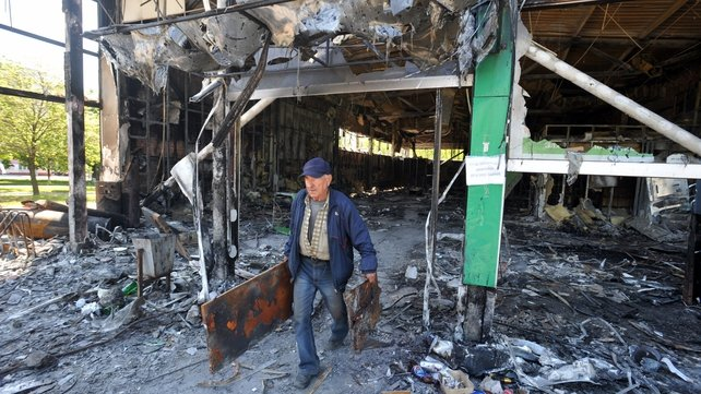 A man carries debris from a bank burned by pro-Russian activists in Mariupol