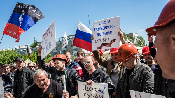 A group of miners rally in front of a regional administrative building occupied by pro-Russian supporters in Donetsk