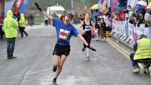 A runner shows his delight at the finish of the Belfast City Marathon
