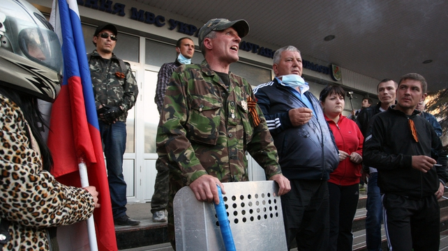 Pro-Russian activists gather on the steps of the Regional Interior Ministry building in Luhansk