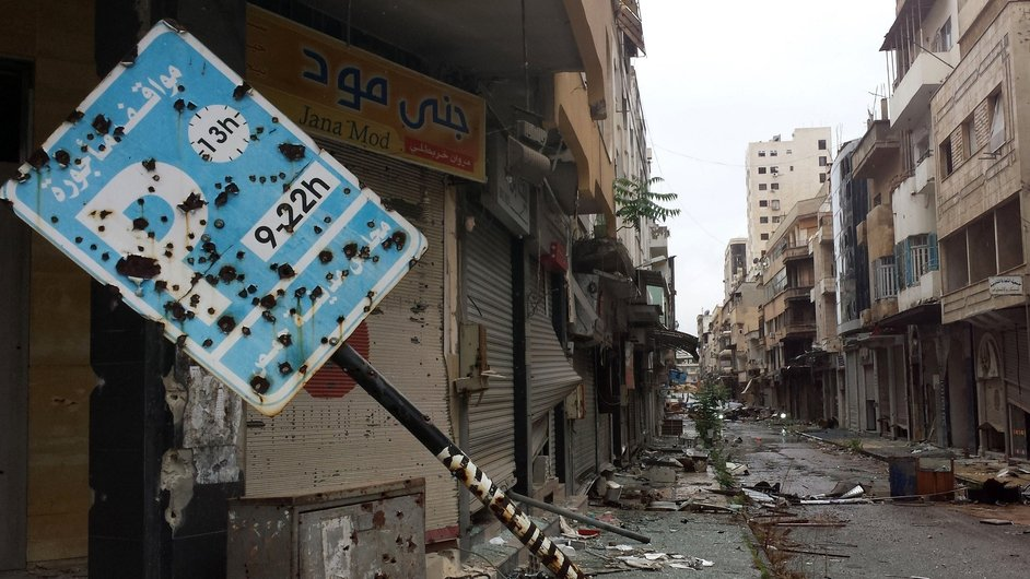 A bullet-riddled parking sign stands amid debris in a deserted street leading into the old city of Homs, Syria
