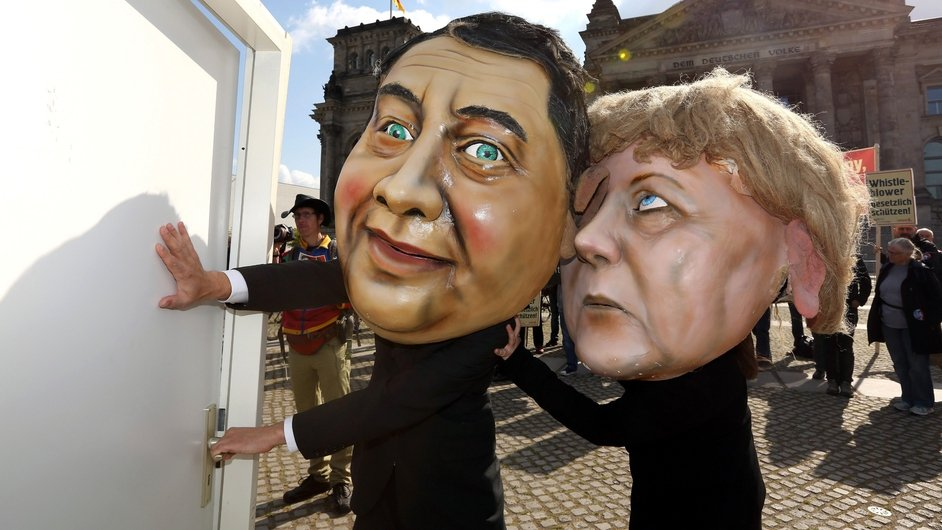 Activists wearing masks of German Chancellor Angela Merkel and vice chancellor Sigmar Gabriel demonstrate in favour of an appearance by Edward Snowden at the German Bundestag