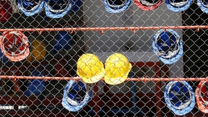Construction workers' helmets hang on a fence at a site in Thailand